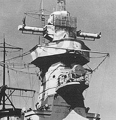 The uppermost structure is the revolvable Gun Director, the long arms being part of the original optical system. The added radar 'mattress' is clearly to be seen.