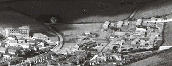 Aerial view: a school and houses to the left and the RAF camp to the right.
